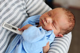 Newborn baby boy in parent's arms with thermometer