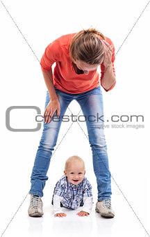 Young Caucasian mother and baby boy playing over white