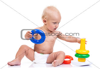 Cute little boy playing with pyramid toy over white