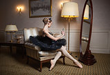 Ballerina in black tutu sitting in armchair in front of mirror and taking self portrait with camera on her cell phone