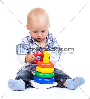 Cute little boy playing with pyramid toy over white background