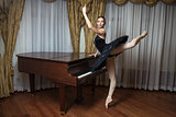 Ballerina in black tutu standing on pointes at grand piano