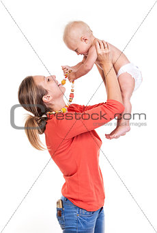 Young Caucasian woman lifting her baby son over white, boy playing with nursing necklace