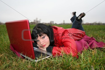 black head woman is laying on a plaid in park grass with notebook