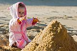 Child reaching for a sand on the beach