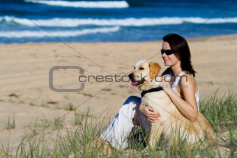 Young female with a dog sitting at a beach