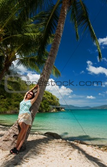 Girl under a palm tree in a tropical paradise