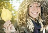 Young smiling woman holding autum leaf