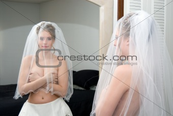 Autumn Bride covering her breast with veil on looking in mirror.