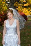 Autumn Bride in park near colorful trees.