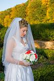 Autumn Bride looking down at her bouquet at the park.