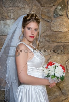 Autumn Bride with bouquet in front of stone wall.