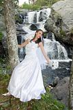 Bride in wedding dress at waterfall with bouquet.