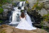 Bride looking at waterfall with veil in her hand.