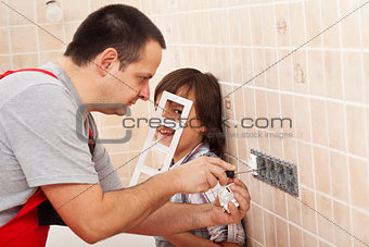 Boy assisting his father in electrician work