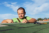 Installing the last strip of bitumen roof shingles
