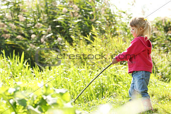 beautiful little girl in nature playing with a stick