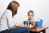 Mother explains to daughter purpose of the chess pieces