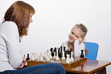 Mother explains daughter purpose of the chess pieces