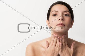 Beautiful woman massaging her throat