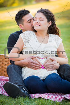 Pregnant Hispanic Couple Making Heart Shape with Hands on Belly
