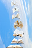 stack of books fly in blue sky