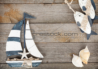 Toy sailboat and fish with seashells on a wooden background