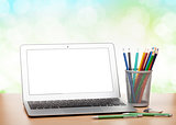 Laptop with blank screen and colorful pencils