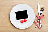 Valentine's Day blank photo frame over plate and silverware