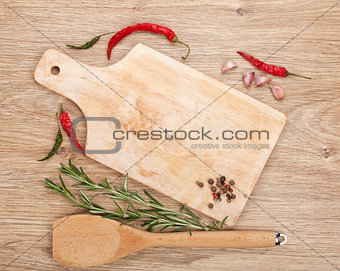 Cutting board with spices around over wooden table
