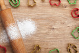 Rolling pin with flour and cookie cutters on wooden table