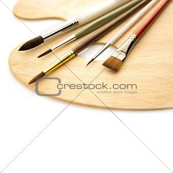 Art brushes with wooden palette isolated