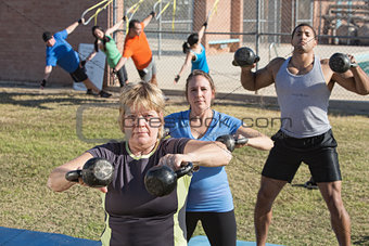 Mature Woman and Group Exercising Outdoors