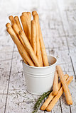 white bucket with bread sticks grissini and rosemary