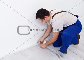 Painter worker preparing the room - laying protection film