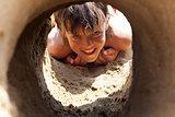 Happy boy on the beach looking through sand castle tunnel