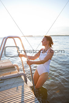 Attractive woman climbing ladder to pier