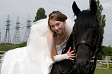 fiancee in a wedding dress astride on a horse