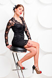 Charming girl in a black dress on a chair