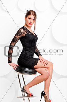 beautiful girl in a little black dress on a chair