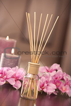 air freshener sticks at home with flowers and ou of focus backgr