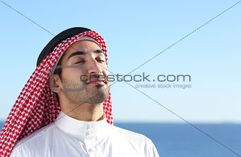 Arab saudi man breathing deep fresh air in the beach