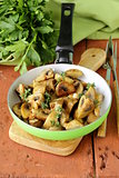 fried champignon mushrooms with thyme in a pan