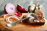 Fork with anchovies, rye bread and red onion.