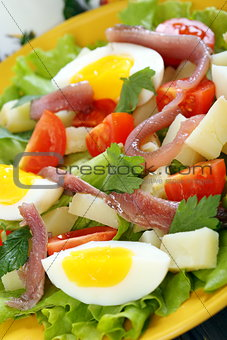Salad with eggs, cherry tomatoes and anchovies.