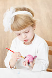 little girl painting egg