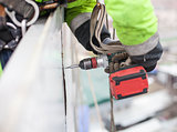 Closeup of industrial climber with screwdriver on metal construction
