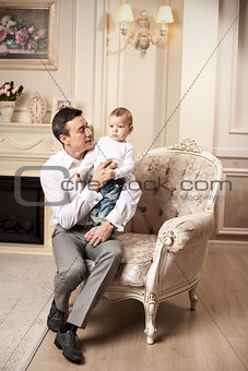 Young man with son sitting in armchair in living room