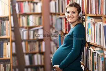 Young pregnant woman in headphones looking at camera while standing in library