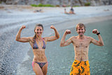 Young woman and man flexing their muscles jokingly while resting at beach